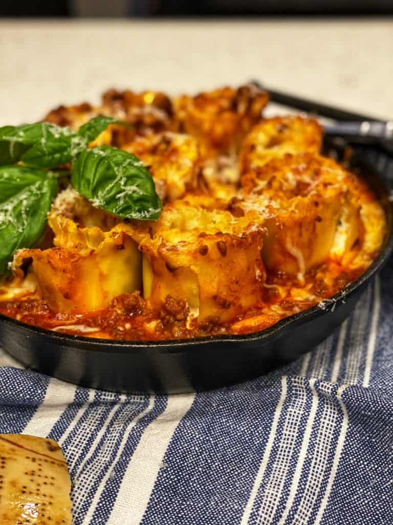 a cast iron pan full of lasagna rollups