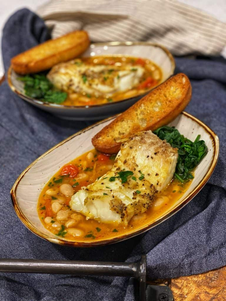 two bowls filled with pan seared halibut in a spicy tomato broth with spinach and toast