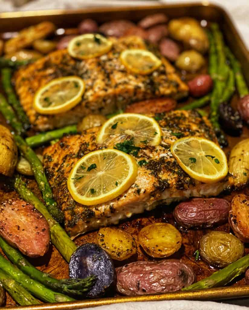 a pan of herb and honey glazed salmon topped with lemon slices surrounded by potatoes and asparagus
