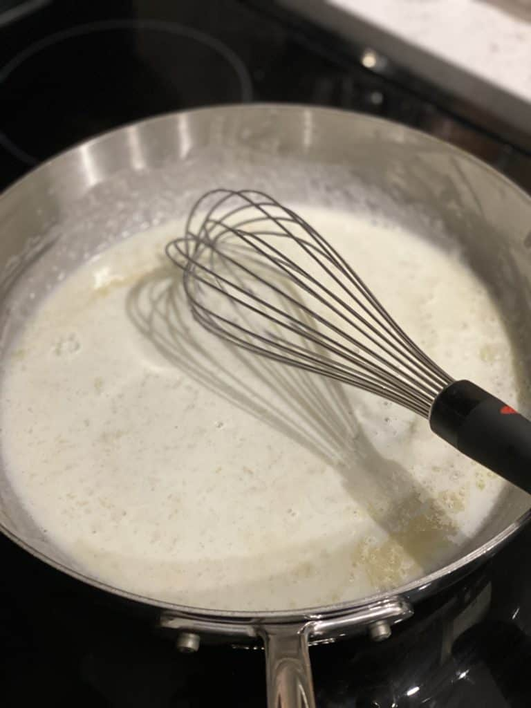whisking milk in a pan with butter and flour