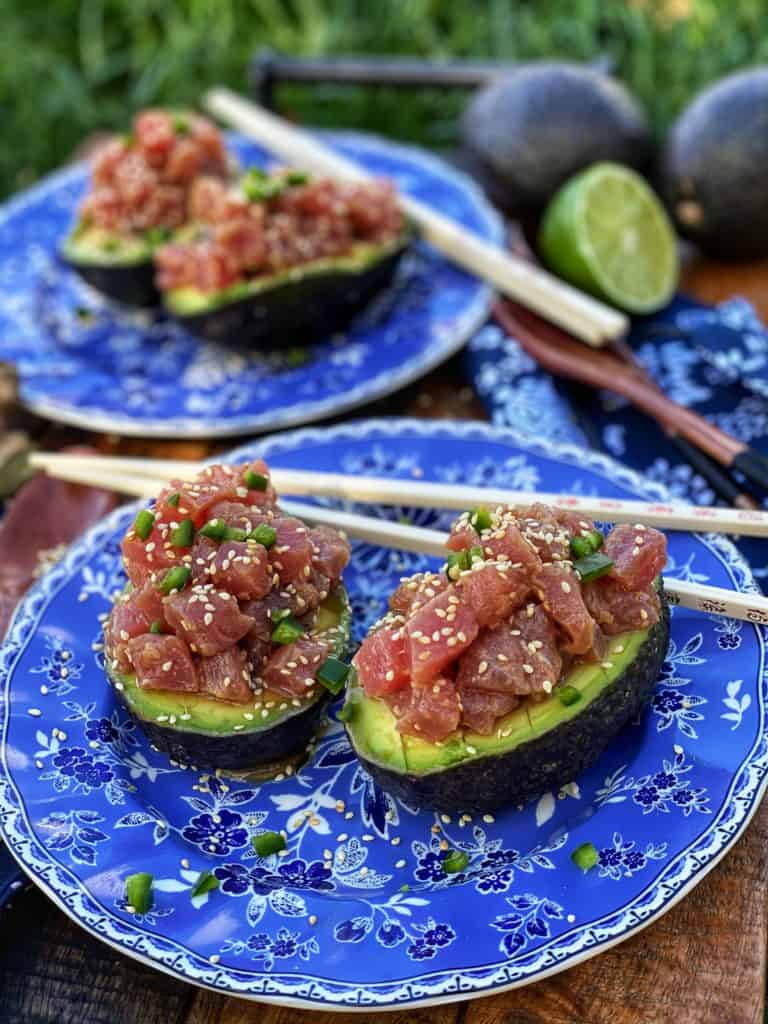 four avocados on blue plates filled with tuna tartare