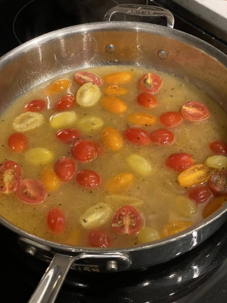 halved cherry tomatoes in a pan with white wine and chicken broth
