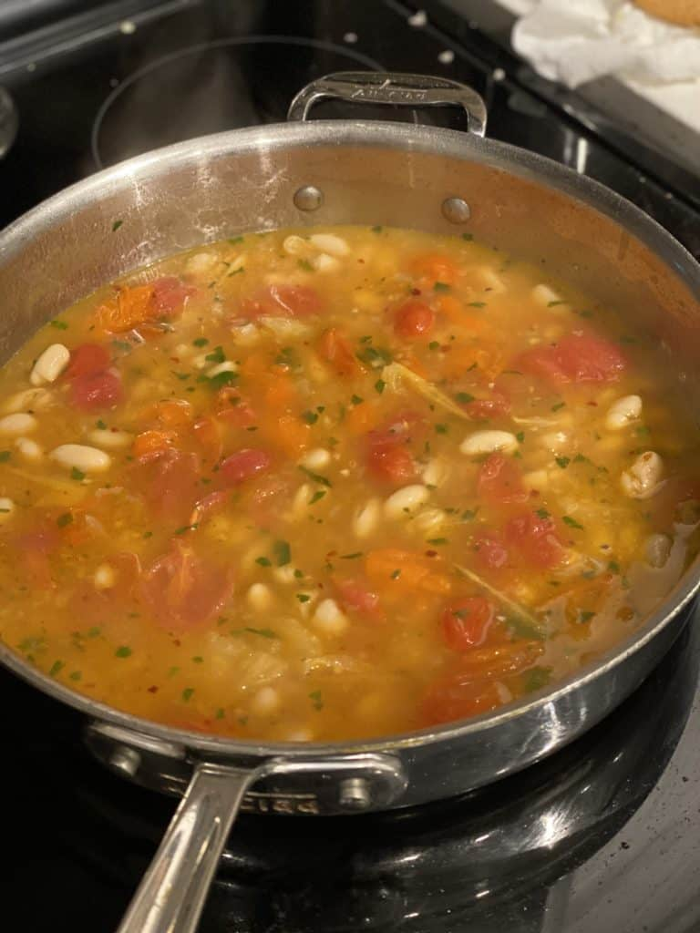 spicy tomato broth with cannellini beans in pan