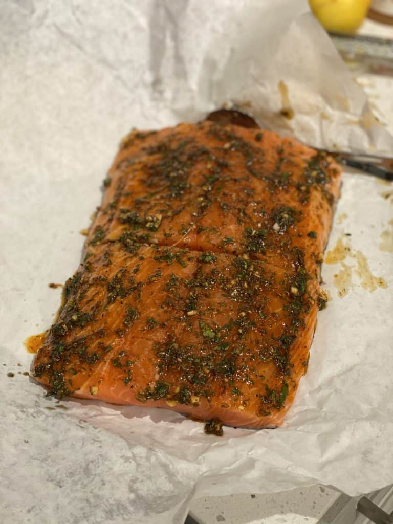 a piece of salmon covered in an herb and honey rub