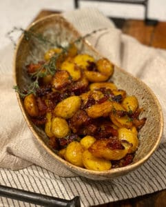 a bowl of maple roasted potatoes and bacon with fresh thyme sprigs