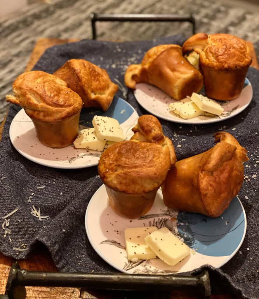 three plates filled each with two Gruyère and black pepper popovers with butter