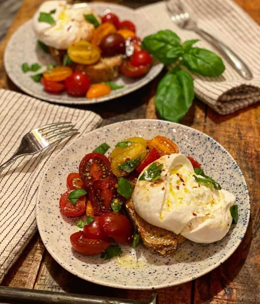 two plates of burrata toast with tomatoes