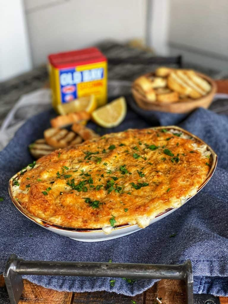 an oven-safe dish filled with hot crab dip with a container of Old Bay seasoning in the background and crostini