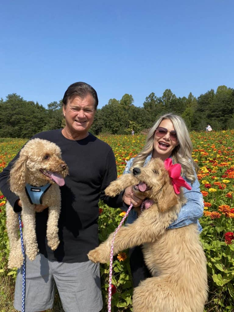 Family photo with my husband holding our mini goldendoodle 7 and me holding our puppy, Hazel in a field of flowers