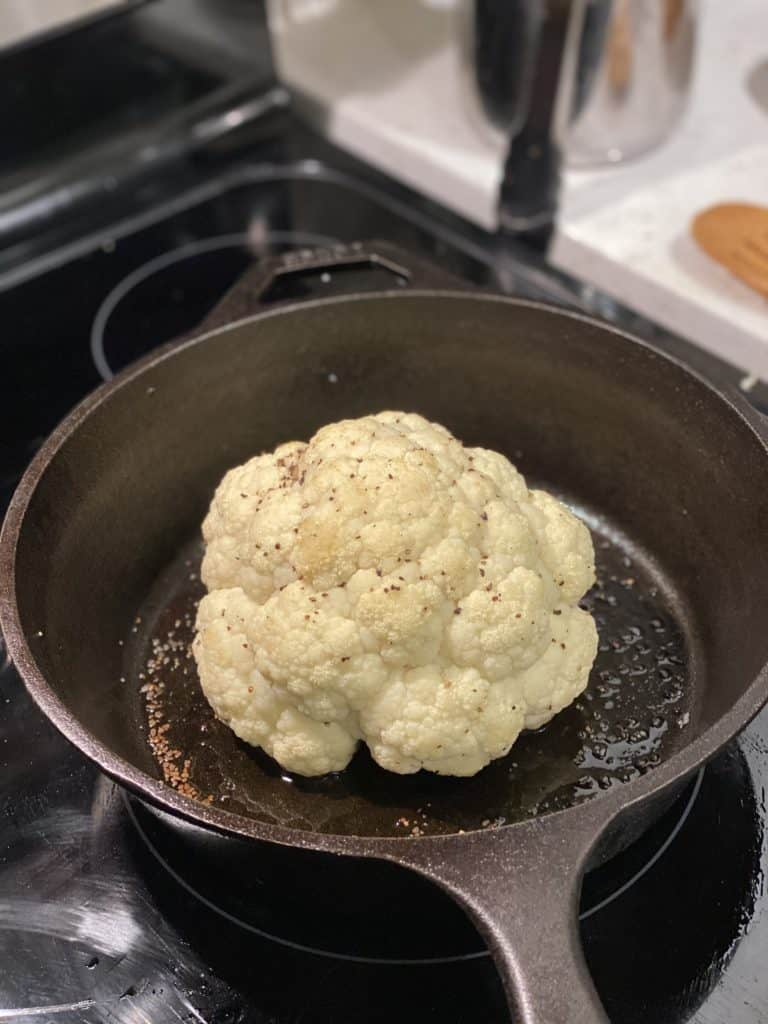a head of roasted cauliflower in a cast iron pan