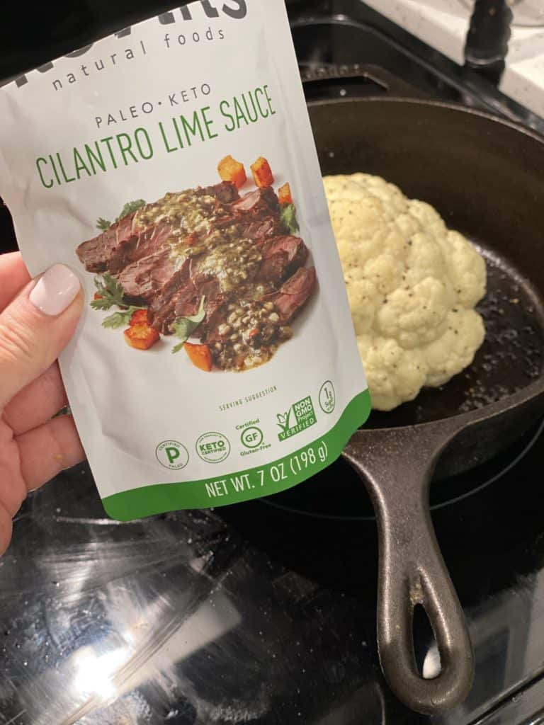 a pouch of cilantro lime sauce with a head of roasted cauliflower in the background