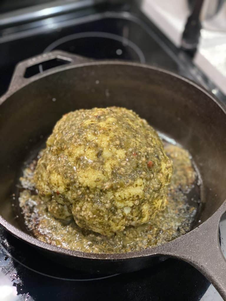 a head of cauliflower brushed with cilantro lime sauce in a cast iron pan