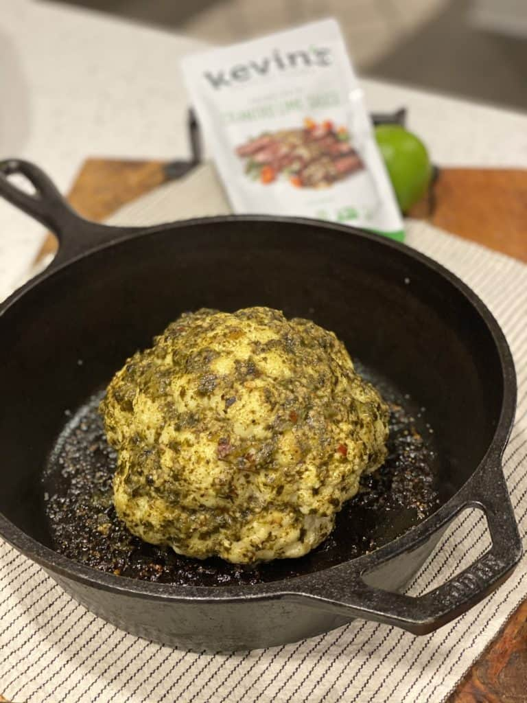 a head of cilantro lime roasted cauliflower in a cast iron pan