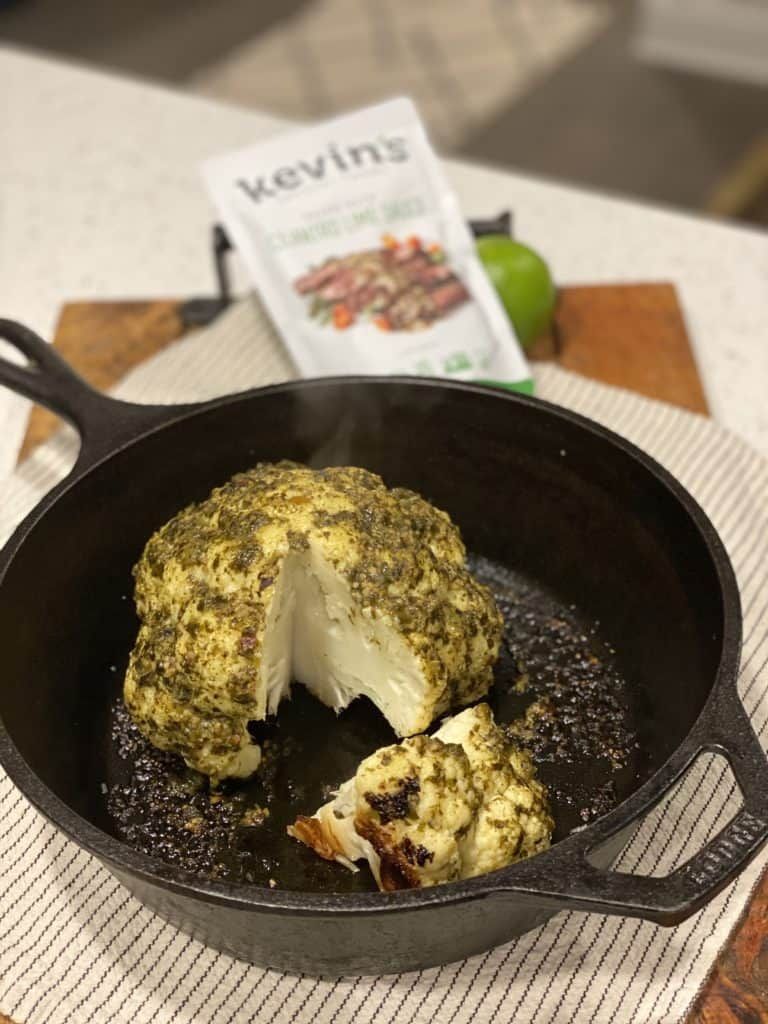 a head of cilantro lime roasted cauliflower in a cast iron pan with a pouch of Kevin's sauces in the background