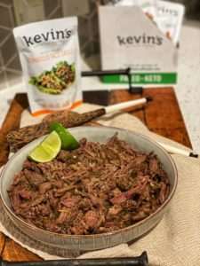 a bowl of tomatillo taco shredded beef garnished with lime wedges with a pouch of Kevin's Natural Foods sauce in the background