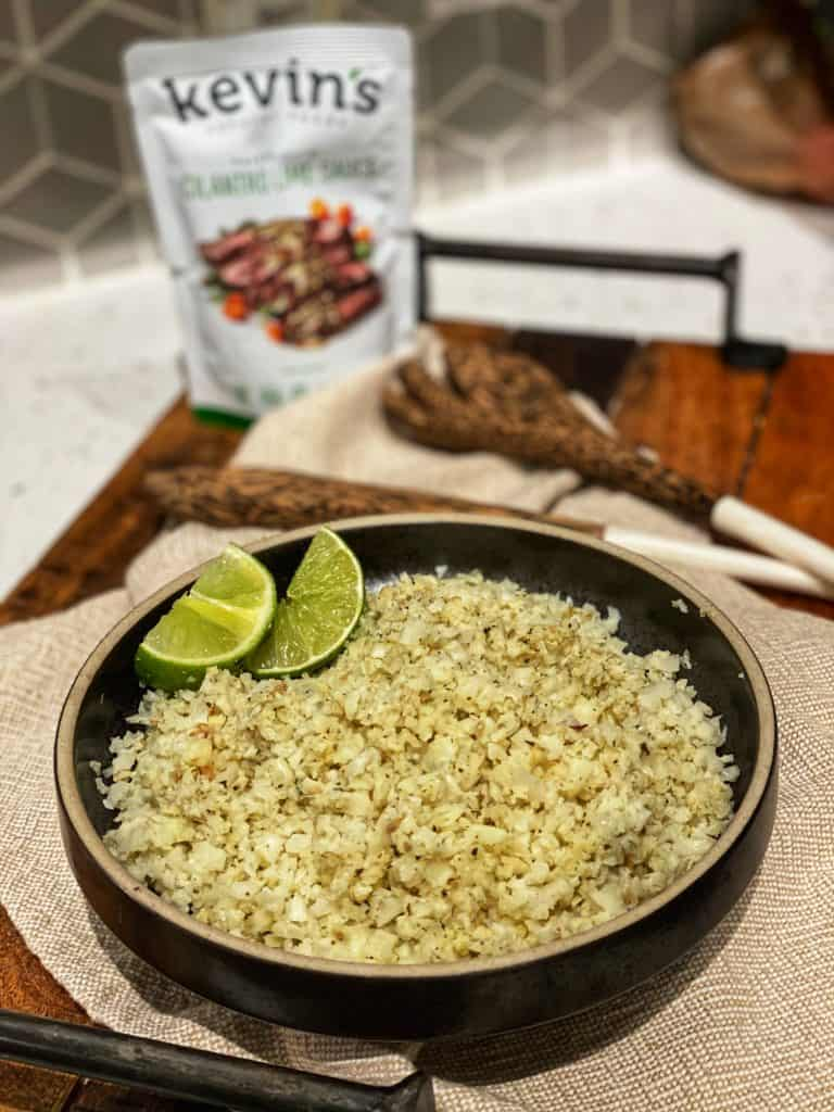 a bowl of Cilantro Lime Roasted Cauliflower Rice with lime wedges and a pouch of Kevin's Natural sauces in the background