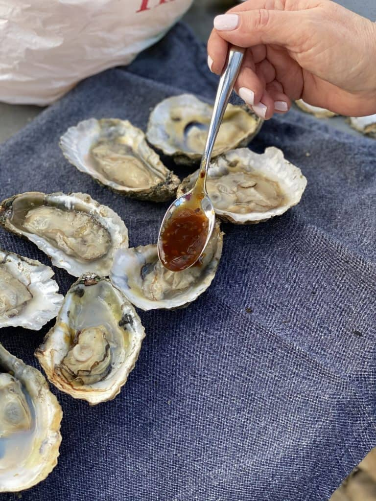 spooning Kevin's Korean BBQ sauce into raw oysters on the half shell