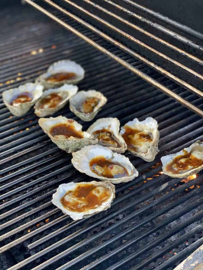 ten raw oysters topped with Kevin's Korean BBQ sauce grilling
