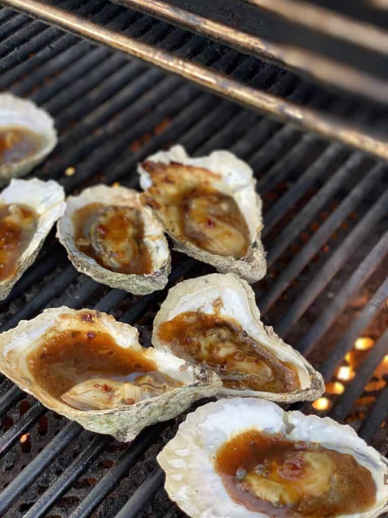 raw oysters topped with Kevin's Korean BBQ sauce grilling
