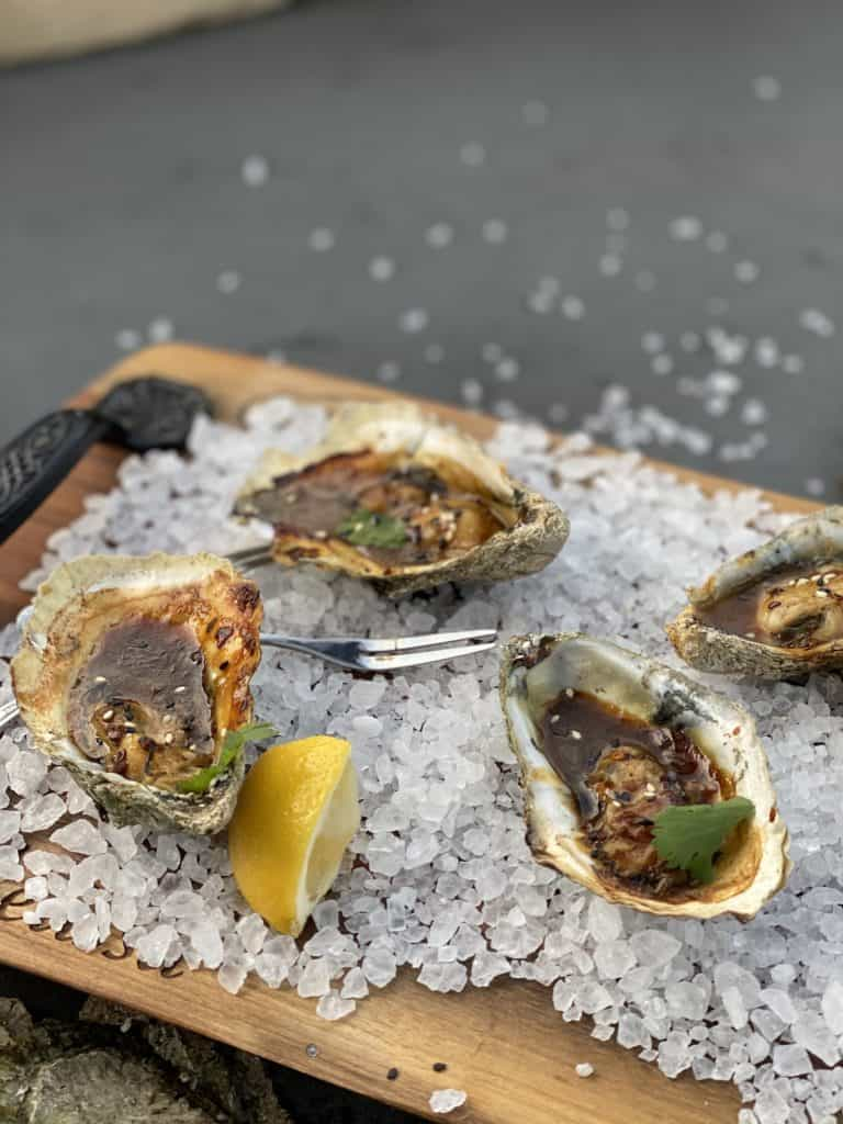 four Korean bbq grilled oysters on a platter with salt and lemon wedges