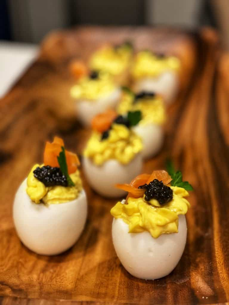 six fancy deviled eggs sitting in a long wooden platter