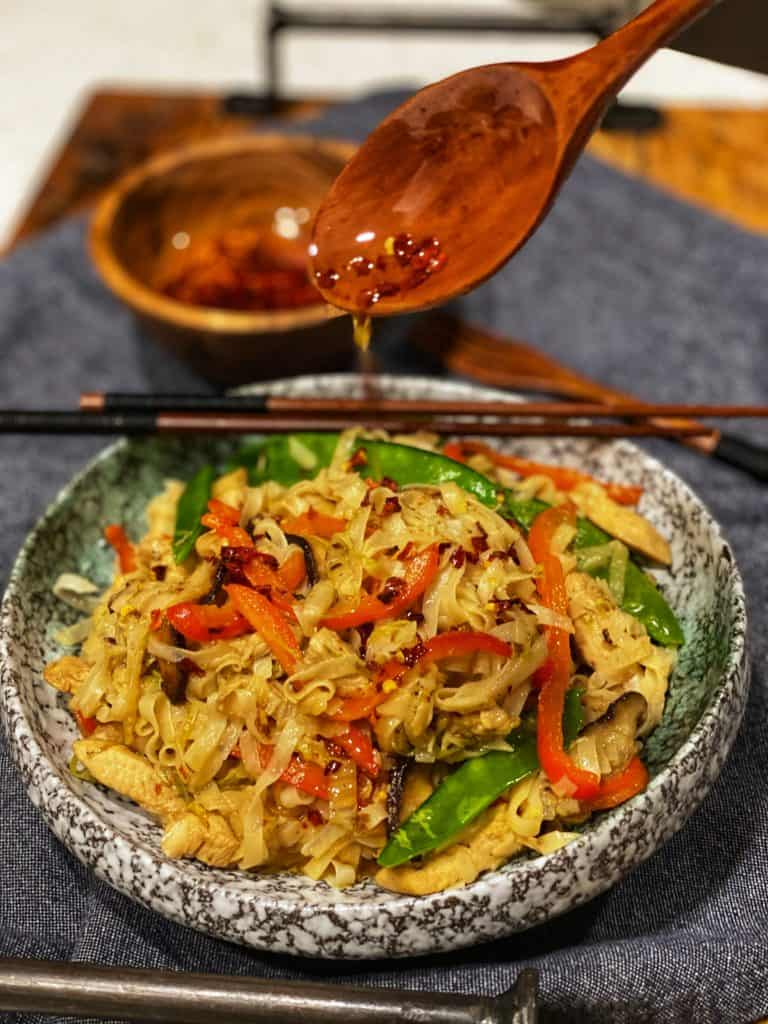 a bowl of hot chili oil noodles with a wooden bowl in the background filled with hot chili oil