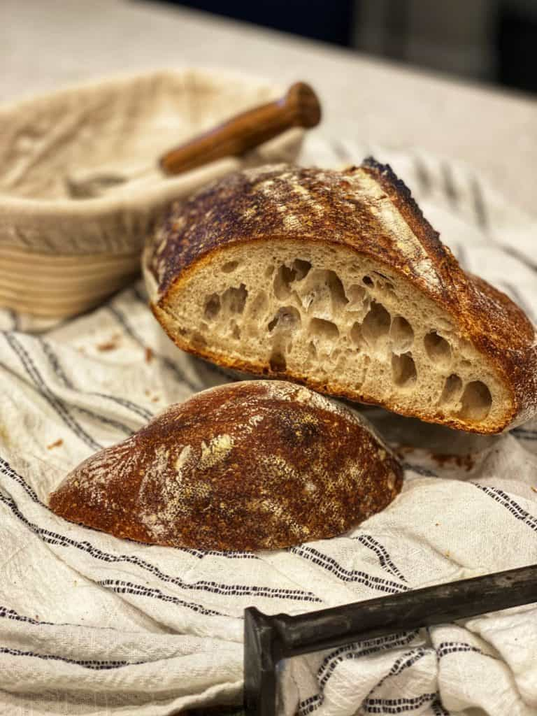a loaf of artisan sourdough bread cut in half showing the inside crumb