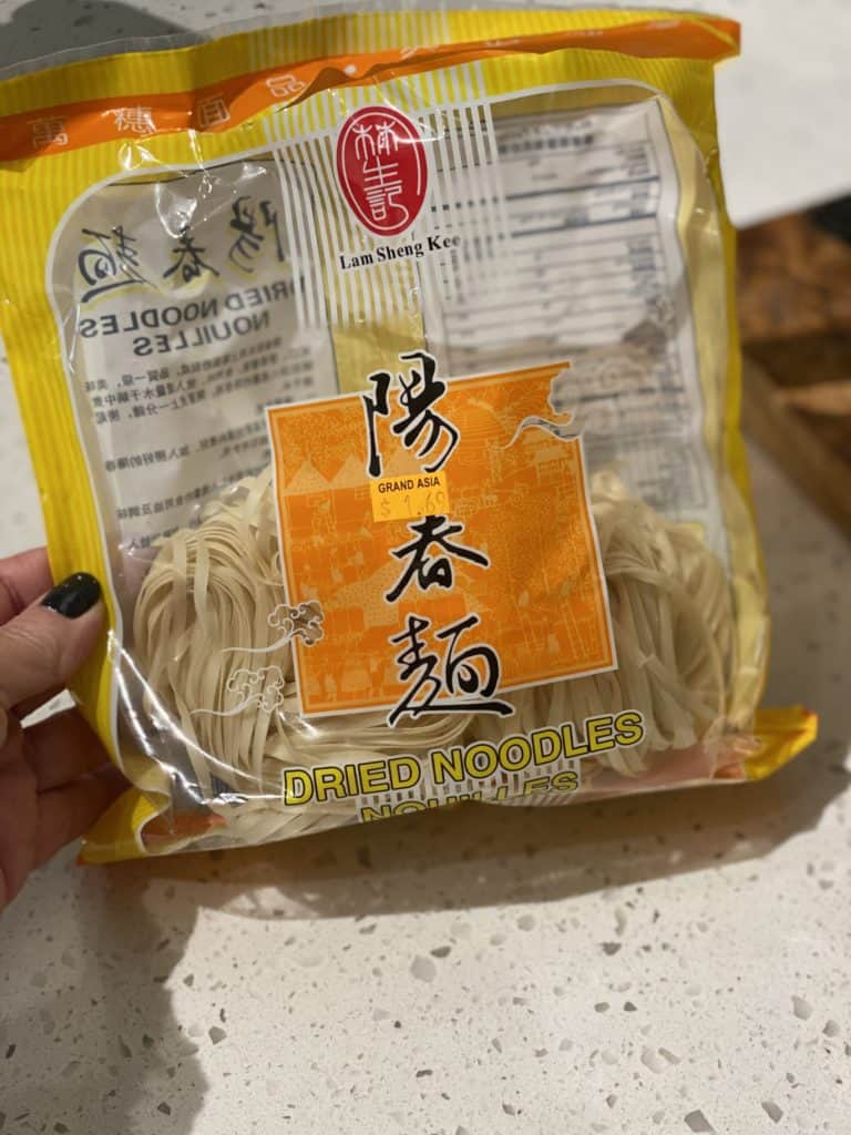 me holding a bag of Asian noodles