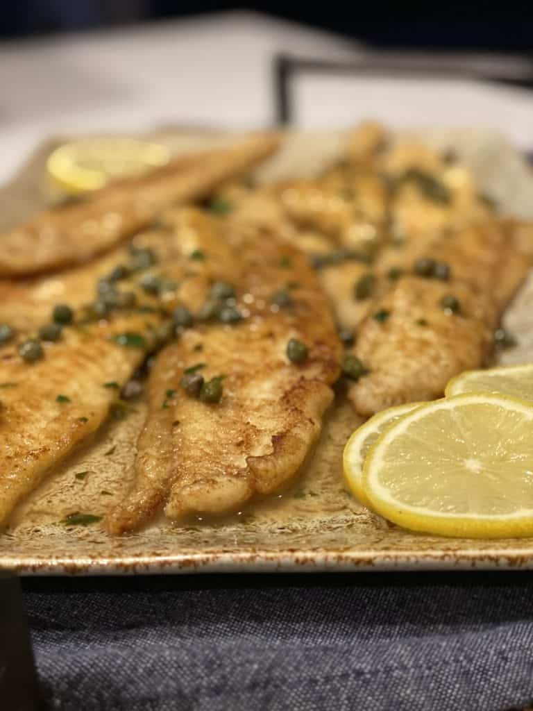 filets of Dover sole sitting on platter prepared in a meunière sauce