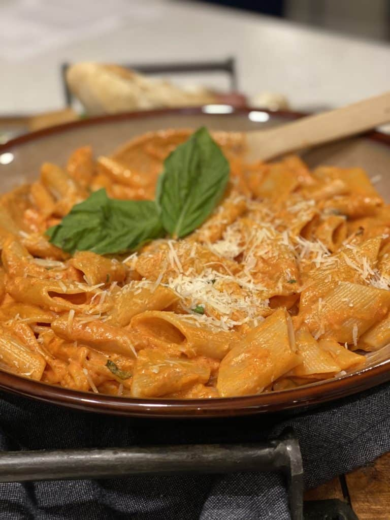 a brown bowl full of penne alla vodka garnish with freshly grated Parmesan cheese and fresh basil leaves