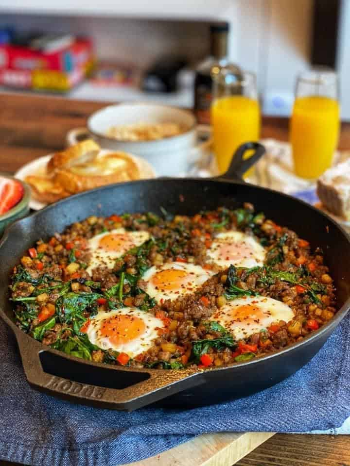 a cast iron skillet of eggs with oatmeal in the background