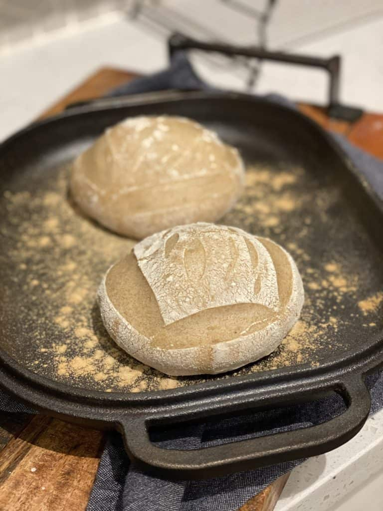 two half baked round sourdough bread bowls sitting in a cast iron pan