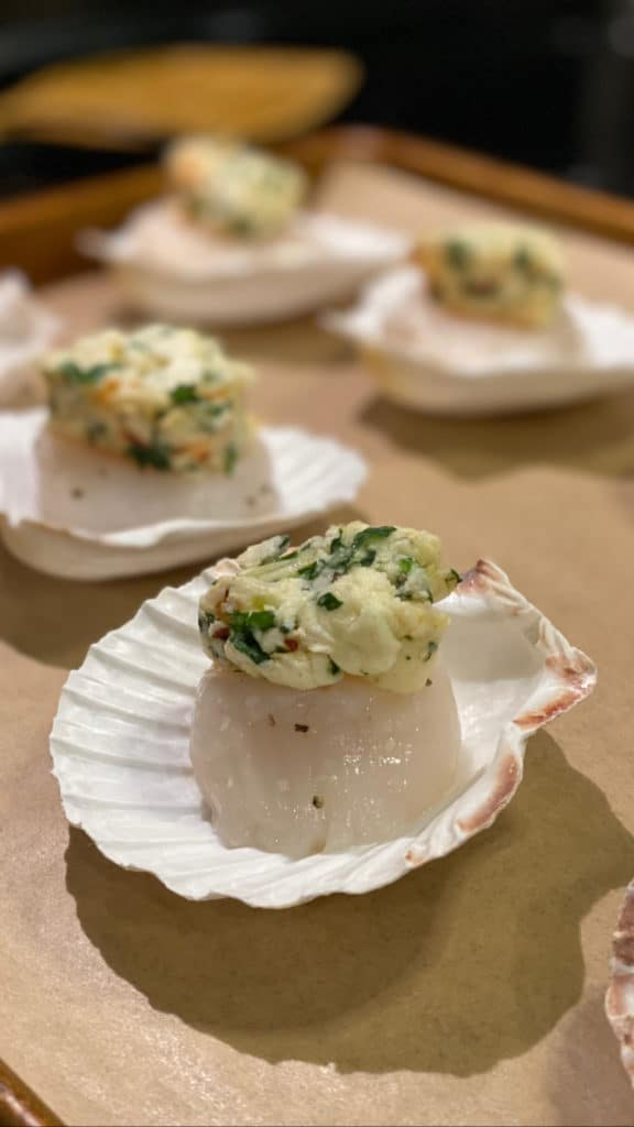 a scallop sitting in a scallop shell topped with a pat of compound butter waiting to be baked on a baking pan