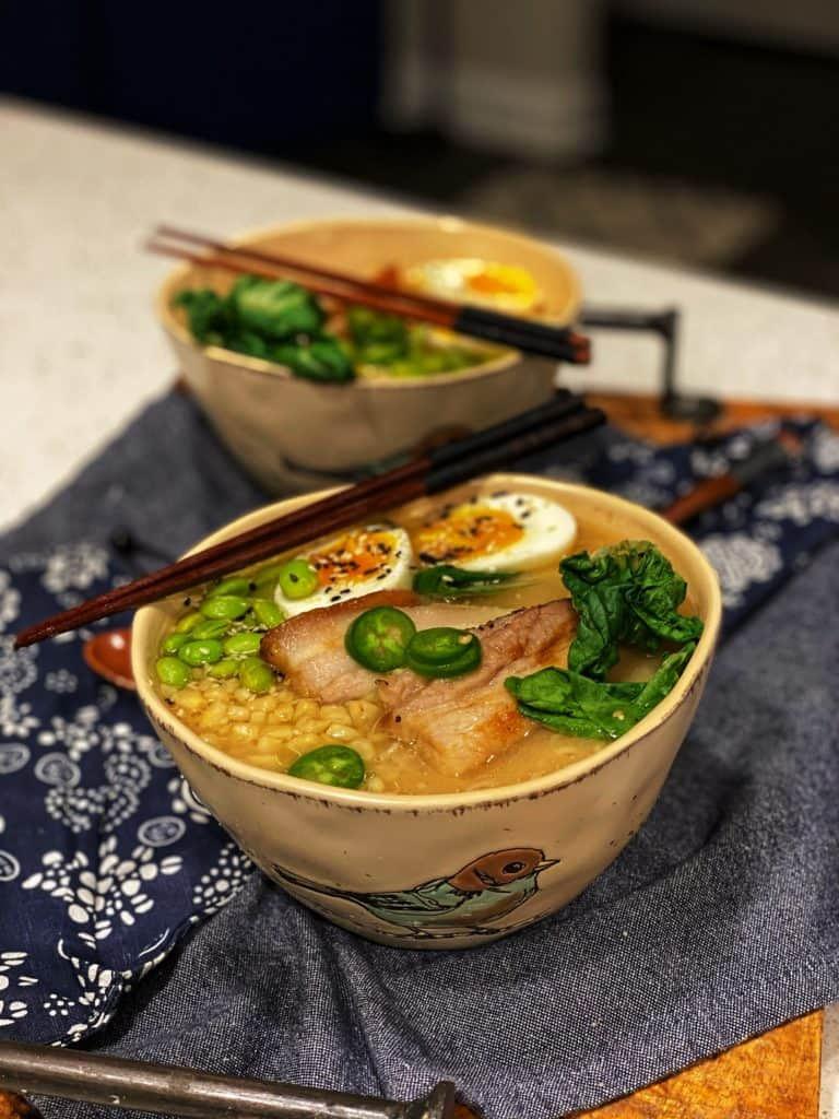 a bowl of quick miso ramen topped with eggs, pork belly, jalapeño slices, edamame and bok choy