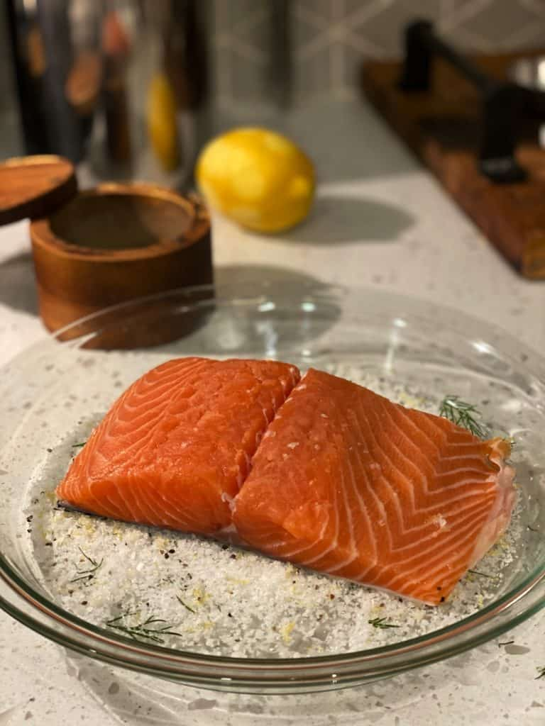 a piece of salmon laying in a glass pie dish for gravlax