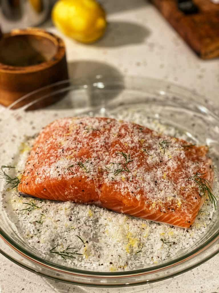 a piece of salmon topped with cure laying in a glass pie dish for gravlax