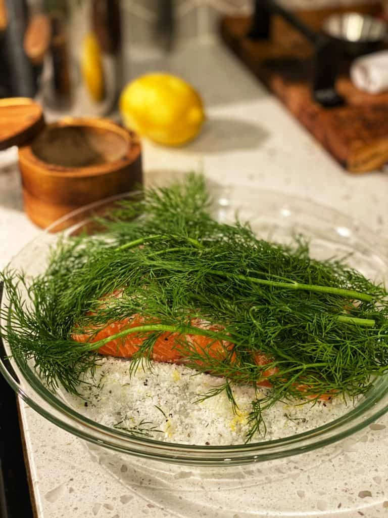 a piece of salmon topped with cure and fresh dill laying in a glass pie dish for gravlax