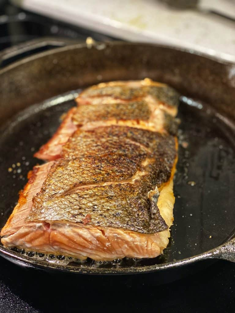 a filet of salmon searing in a cast iron pan skin side up