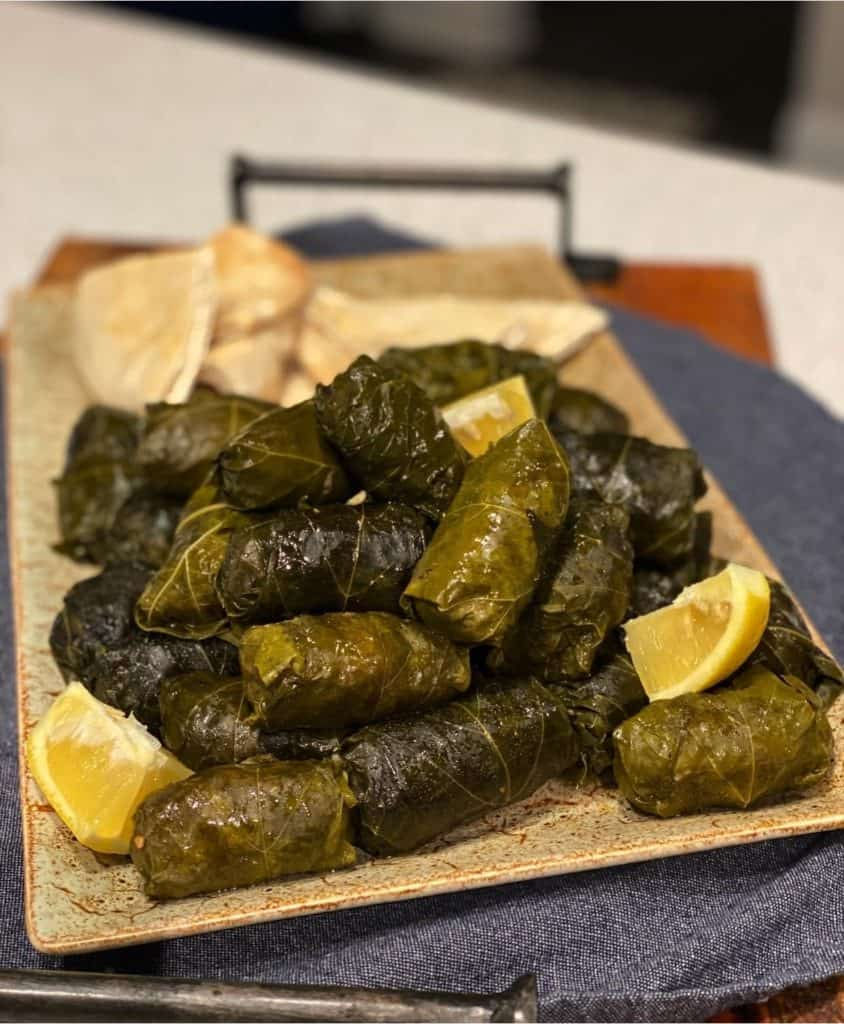 a platter of stuffed grape leaves with lemon wedges