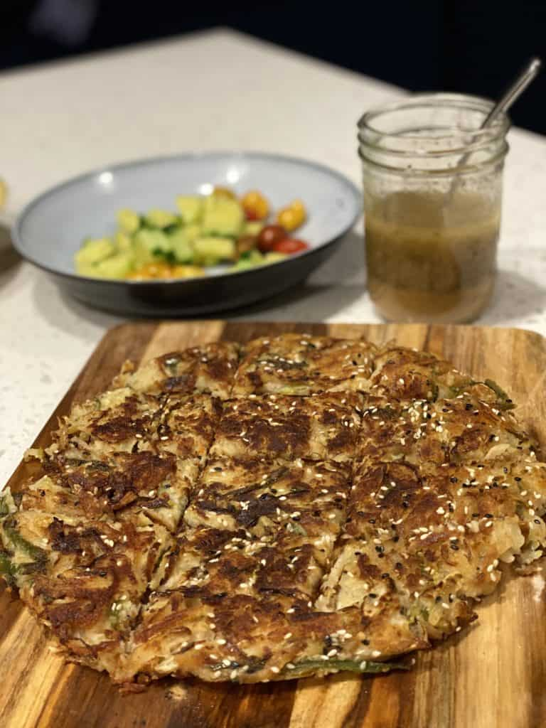 A vegetarian jeon (pancake) on a wooden board with a bowl of salad in the background
