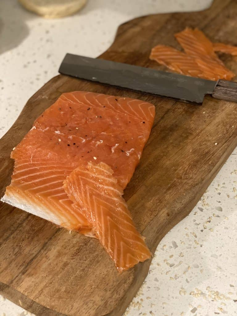 a piece of gravlax on a wooden cutting board with a sharp knife