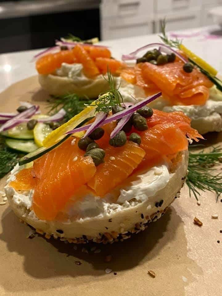 three half of homemade sourdough bagels topped with gravlax, red onion, dill, capers and lemon