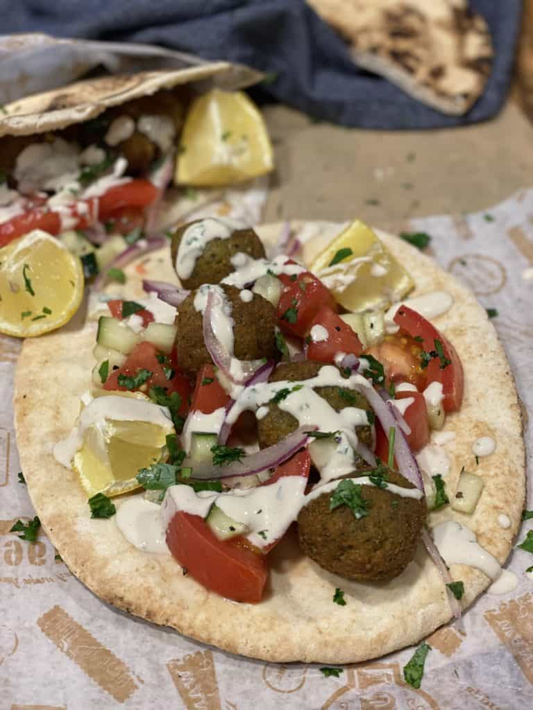 four falafel on pita surrounded by a salad of tomatoes, red onions, lemon and cucumber with tahini sauce drizzled on top