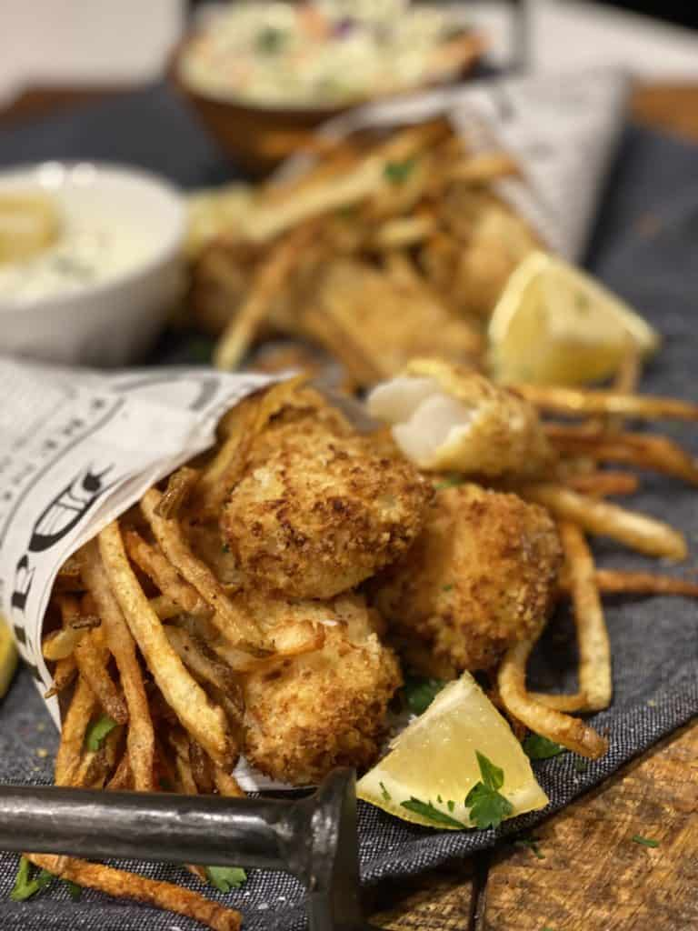 fish and chips in newspaper cones laying on a wooden board garnished with lemon wedges