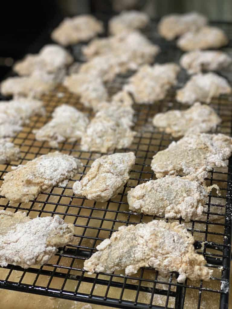 coated shucked oysters coated and drying on a baking rack for oyster po' boy