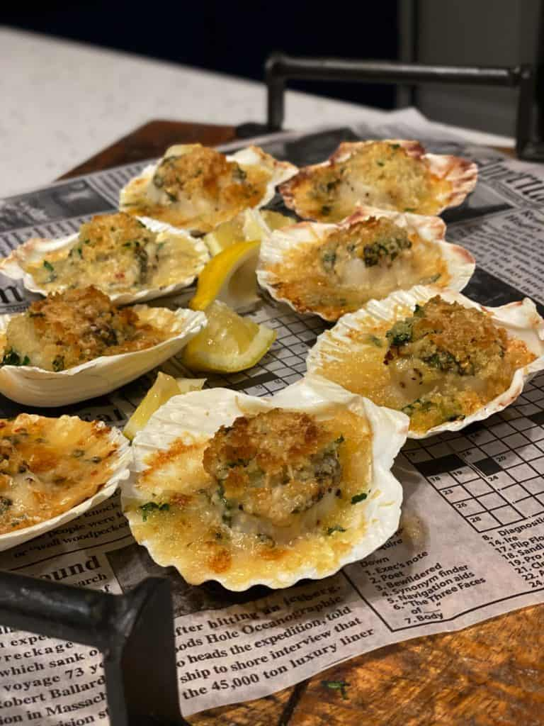 eight parmesan baked scallops sitting on top of a board lined with newspaper
