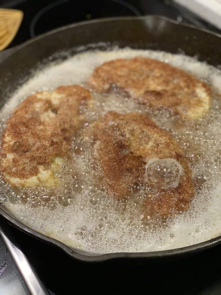 cauliflower steaks frying in a cast iron pan