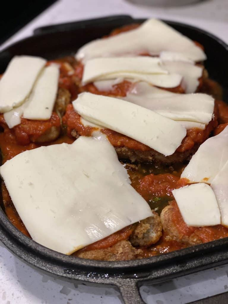 cauliflower steaks topped with sauce and cheese ready to be baked in a cast iron pan for cauliflower parmesan