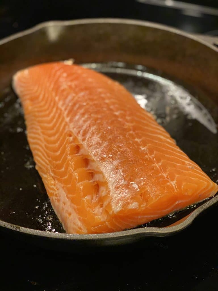 a filet of salmon searing in a cast iron pan flesh side up