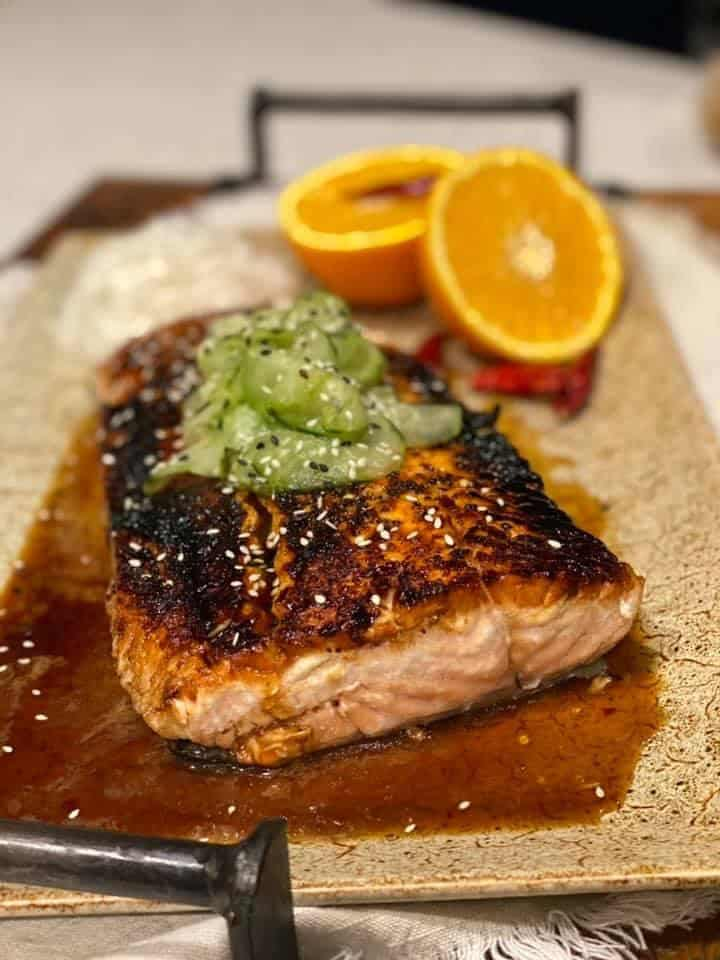 a piece of citrus honey glazed salmon on a platter topped with Asian cucumbers